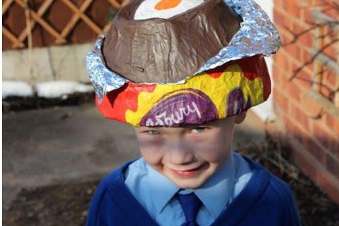 little boy wearing a cadburys creme egg easter bonnet