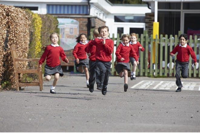 primary school children running in playground