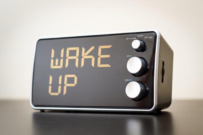 Alarm clock with digital display reading 'wake up'