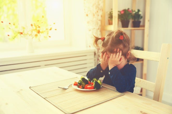 Little girl sitting at a dining table refusing to eat her vegetables