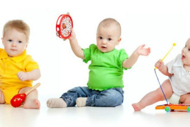 three babies in bright clothes playing with toys