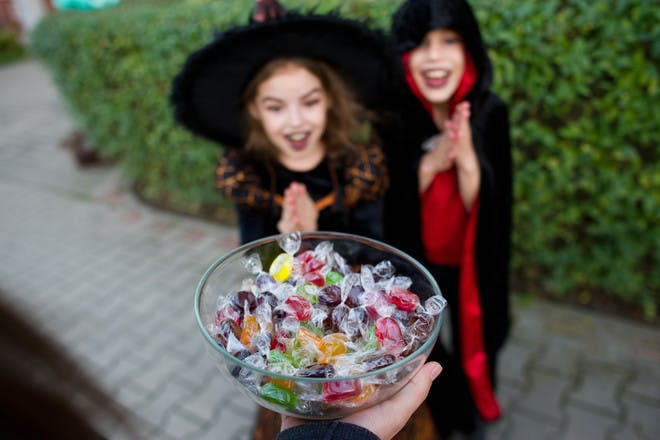 Two kids trick or treating with a bowl of sweets