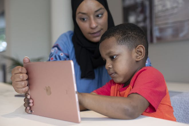Young boy and mum looking at a game on a tablet