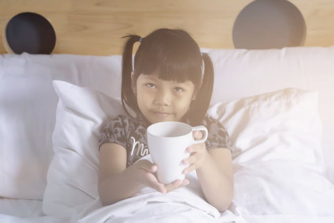 Girl drinking from mug in bed
