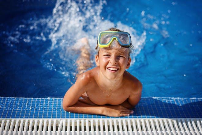 little boy splashing in a swimming pool