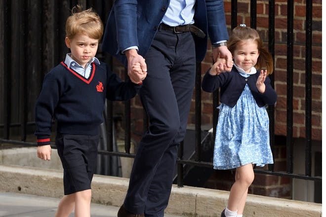 Prince George and Princess Charlotte holding hands with Prince William