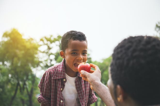 Little boy eating an apple outside