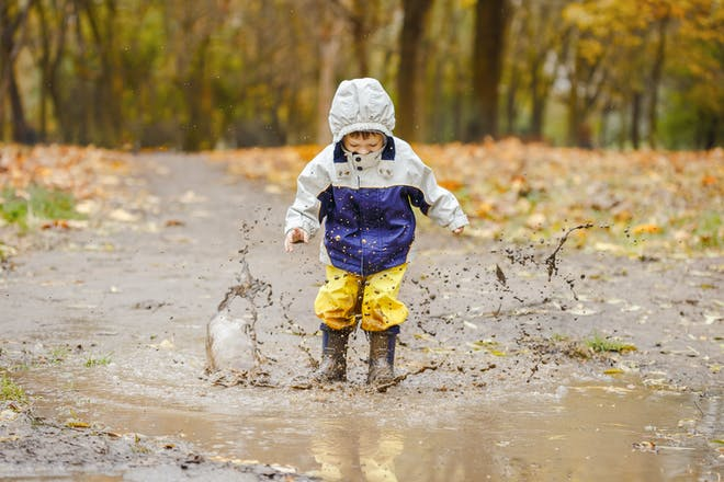 toddler jumping in muddy puddles
