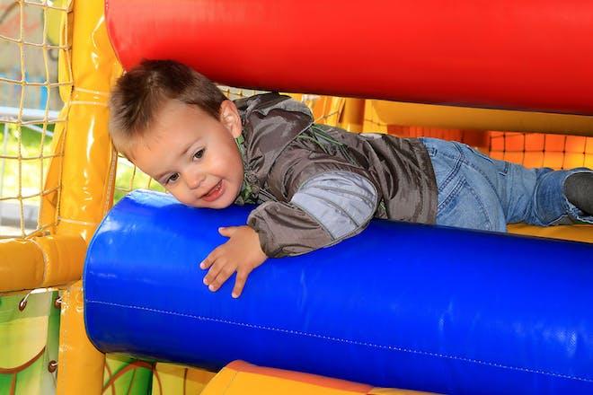 Toddler climbing through tight gap in soft play