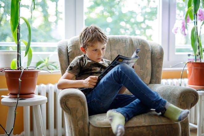 Boy sitting in armchair reading comic