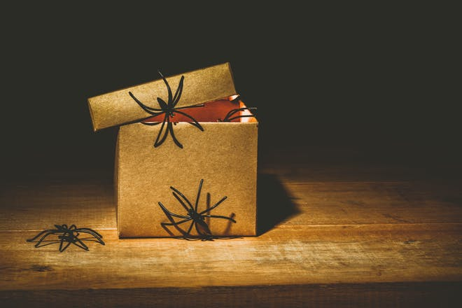 Box decorated with gold wrapping paper and fake spiders for Halloween