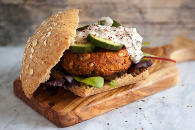 Vegan burger in a bun with salad cucumber and coconut yoghurt dressing