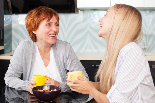 woman and her mother in law sitting in kitchen drinking tea and laughing