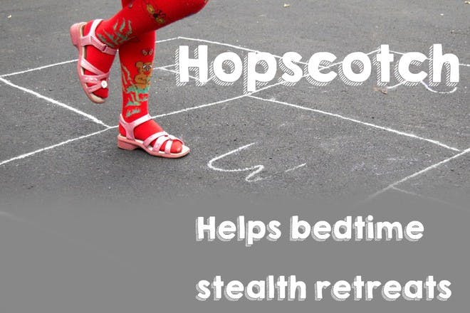 child wearing high red socks playing hopscotch
