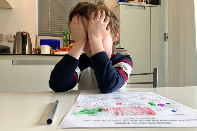 Little boy with hands on face hating homeschooling