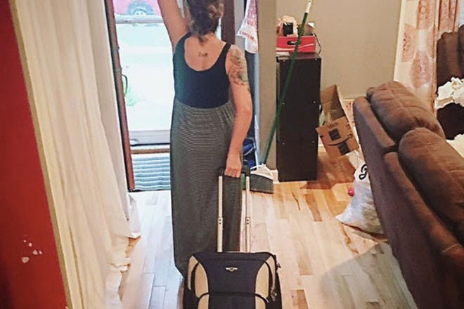 Woman leaving house with suitcase