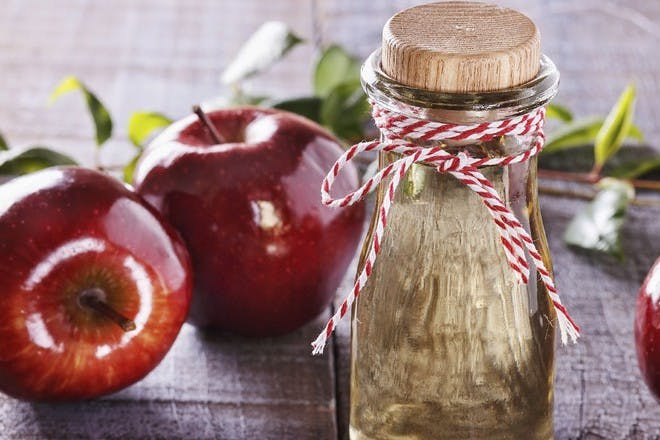 bottle with apples behind it