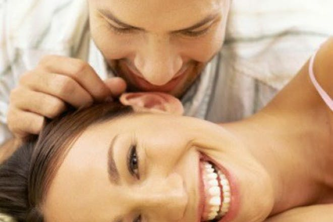 man leaning over woman's ear
