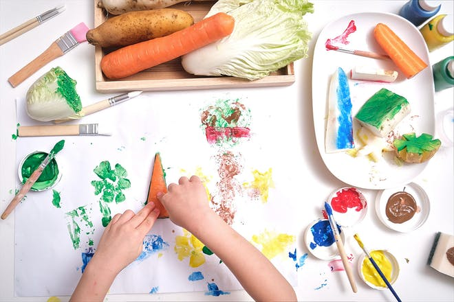 child using different vegetables to paint and print with