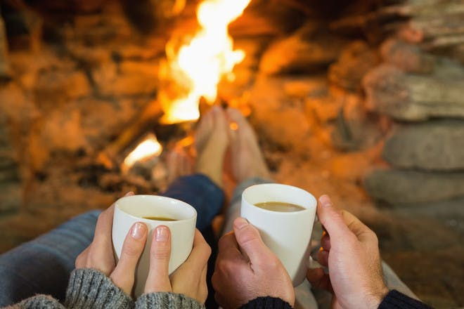 Hands holding hot drinks in front of fire