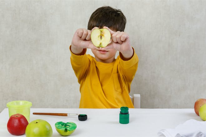 Toddler holding apple ready to paint for 'apple stamp' Halloween craft