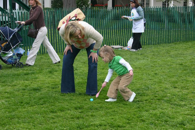 Child and mother egg rolling