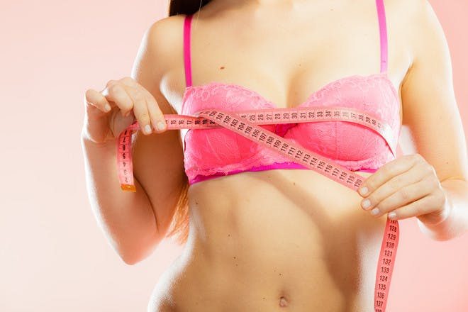 woman in pink bra with tape measure