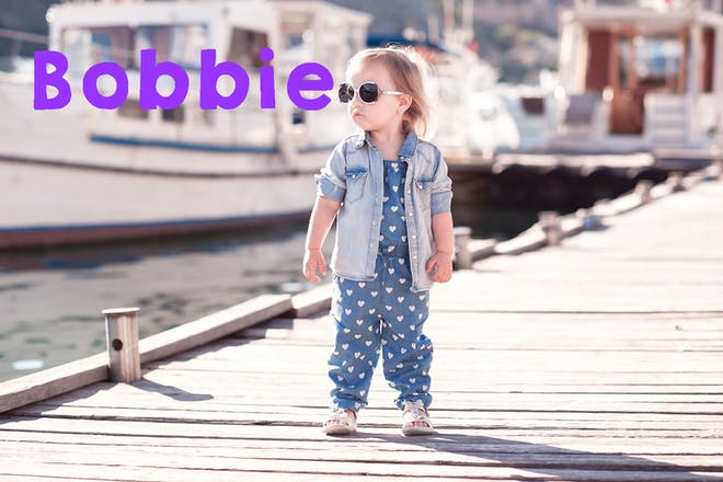 Toddler in sunglasses and denim on jetty. Text says Bobbie