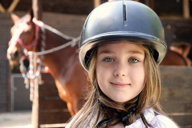 Girl in horse riding helmet with horse in background