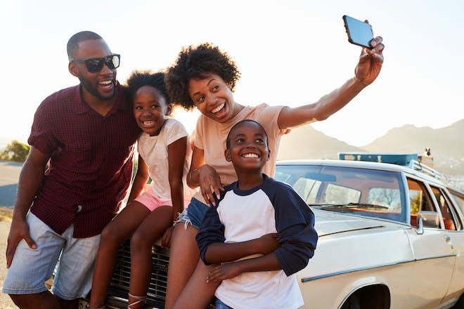 family sitting outside car taking selfie