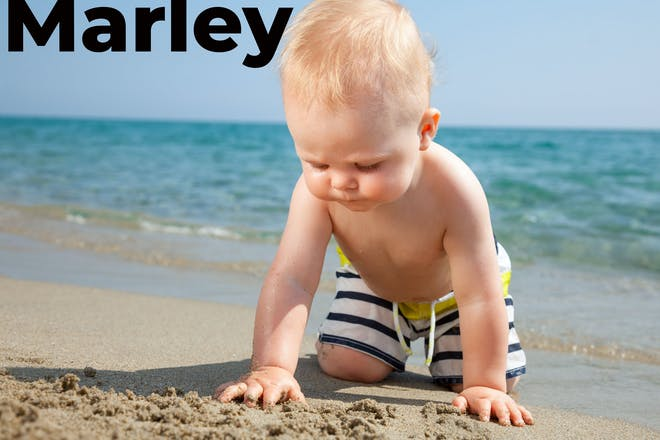 Baby on the beach with Marlley written in text
