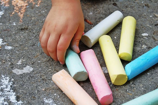 child's hand holding giant outdoor chalk