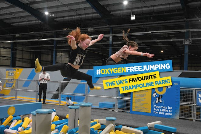 Two girls bouncing over foam pit on trampolines