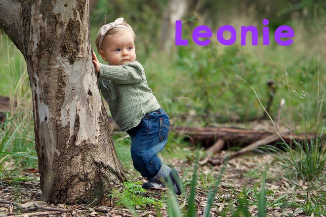 Baby standing and leaning on tree. Text says Leonie
