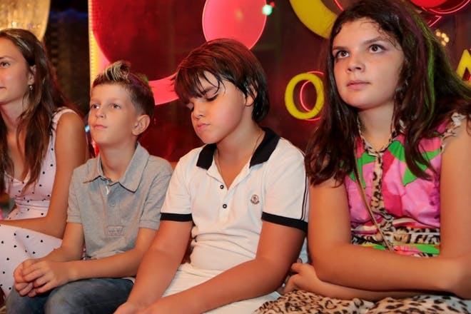 Kids sat on bench at side of disco
