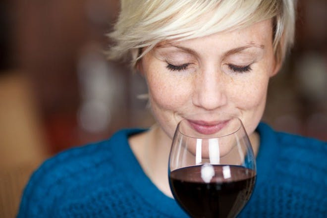 woman in blue jumper holding glass of red wine