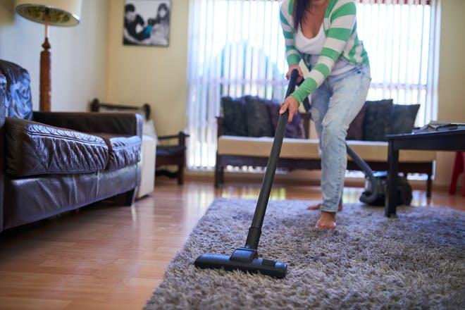 Woman vacuuming rug