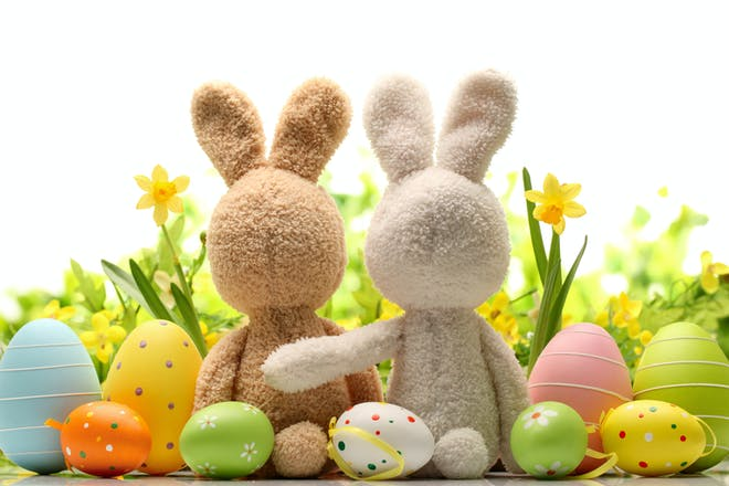 Two toy Easter bunnies with Easter eggs