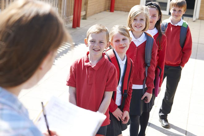 Teacher taking register from group of primary school pupils in playground