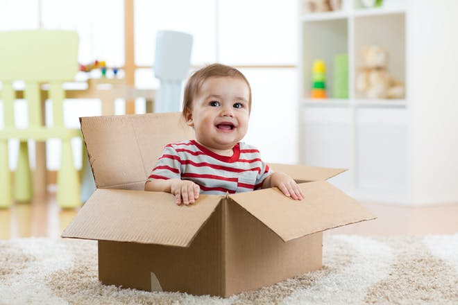 Baby playing in a cardboard box