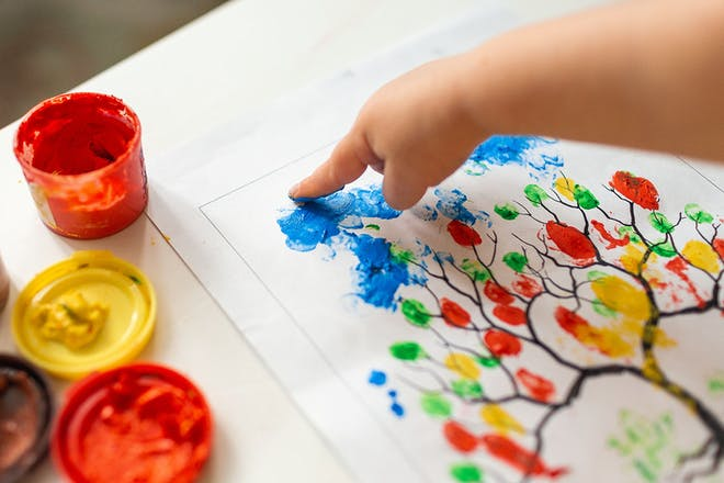 child painting leaves on tree using finger tips