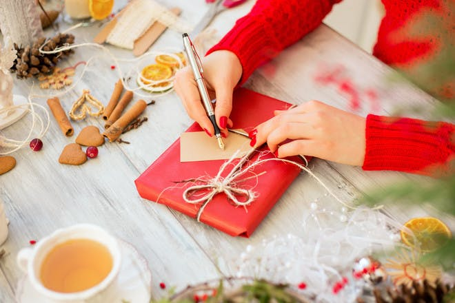 Hands writing label on Christmas present