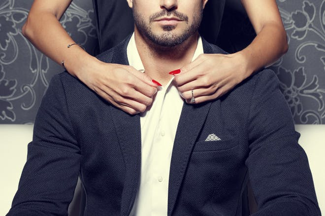 Man in suit with woman's arms around his neck