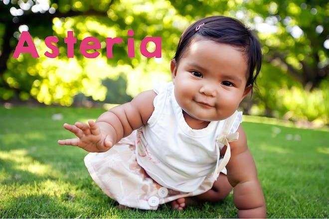 Baby girl on a green garden lawn