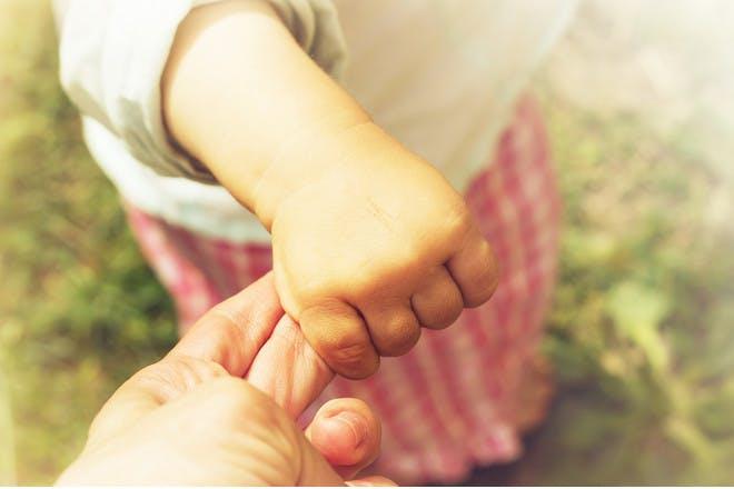 Child's hand holding finger