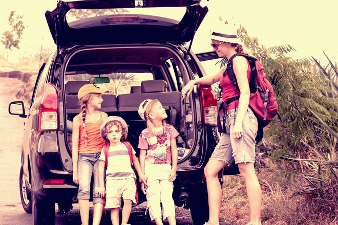 Kids and mum packing up car boot for camping trip