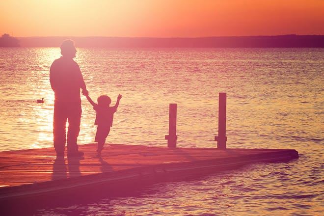 Man and child standing on jetty at sunset