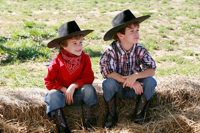 Two little boys dressed as cowboys