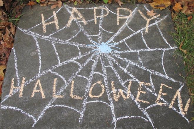 'Happy Halloween' written on the pavement in chalk