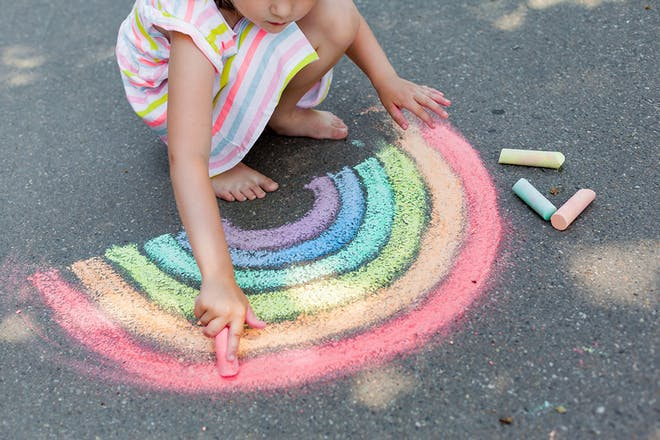 Girl draaing rainbow on pavement using chalk